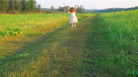 corrida : happy little girl in dress on meadow