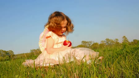 maçãs : little girl eating apple on meadow