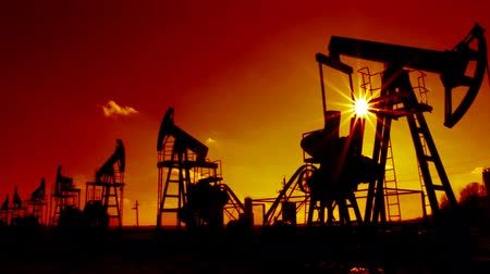 natural resource : row of many working oil pumps silhouette against sun