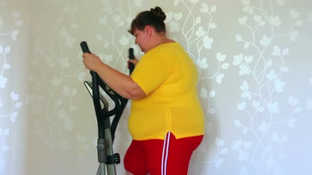 nadváha : overweight woman exercising on trainer ellipsoid