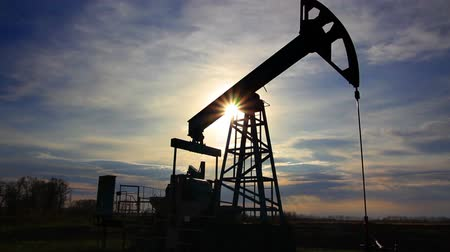 natural resource : working oil pump at sunset