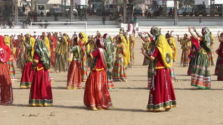 hinduizmus : Indian girls in colorful ethnic attire dancing at Pushkar camel fair India Stock mozgókép
