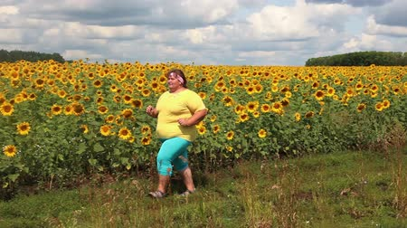 nadváha : fitness - overweight woman running along field of sunflowers Dostupné videozáznamy
