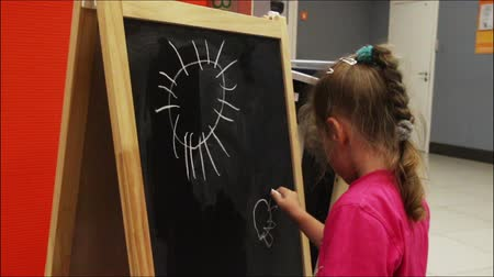lousa : little girl drawing sun with chalk on blackboard Vídeos