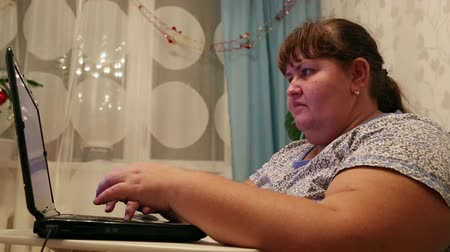 жир : overweight woman typing on computer at home Стоковые видеозаписи