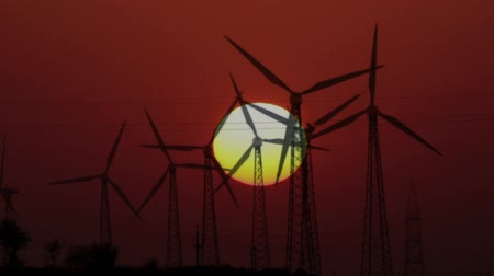 młyn : wind farm - turning windmills on background of setting sun timelapse