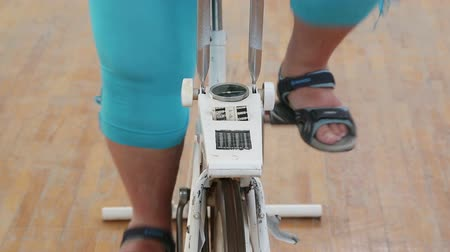 nadváha : overweight woman exercising legs on bike simulator