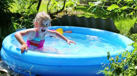 sport dzieci : cheerful girl in inflatable pool in summer garden Wideo