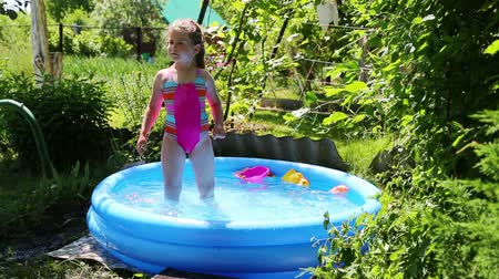 uszoda : cheerful girl in inflatable pool in summer garden - timelapse Stock mozgókép