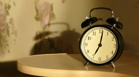 poplach : Vintage alarm clock on nightstand counts the time and then loudly ringing 4k