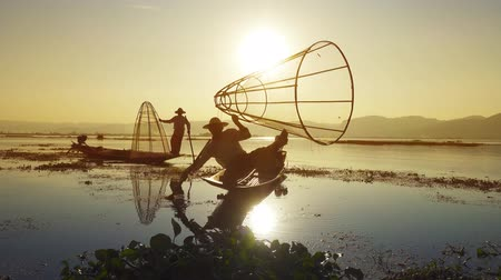 evezés : Myanmar travel attraction landmark - Traditional Burmese fishermen with fishing net at Inle lake in Myanmar famous for their distinctive one legged rowing style, 4k