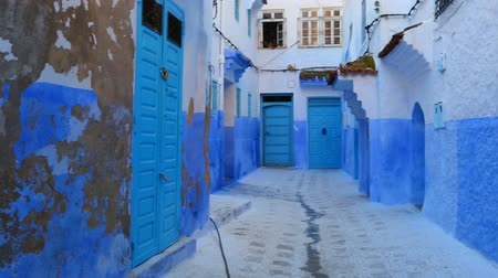 fas : Panorama of traditional old blue street with color pots inside Medina of Chefchaouen, Morocco Stok Video