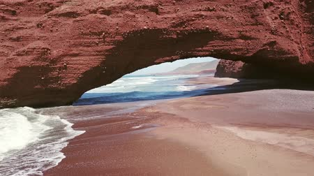 arch rock : Flying through the arch on Legzira beach with arched rocks on the Atlantic coast in Morocco, 4k