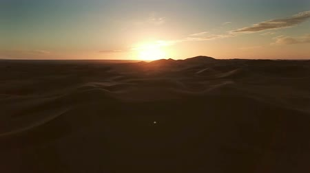 サハラ : Flying over sand dunes in Sahara desert to the rising sun, Africa