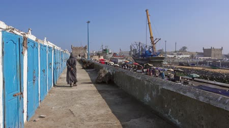 Fisherman walking along fishing lockers in the port of Essaouira, Morocco, 4k