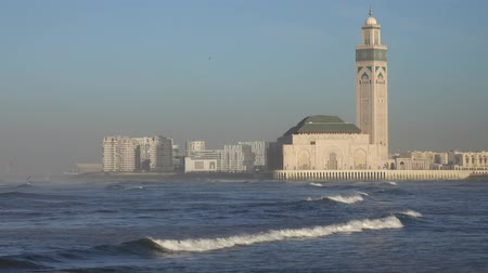 Hassan II mosque in Casablanca and Atlantic ocean waves at sunset, Morocco, panorama 4k