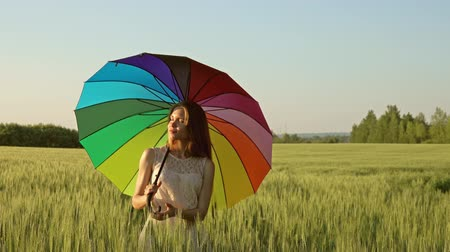 výrazy : Cute girl with a multicolored umbrella in a wheat field at sunset, 4k