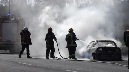blussen : Firefighters extinguish a burning car on the road