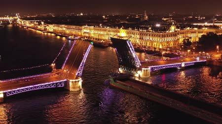 winter palace : Aerial around view of the ship sailing under a drawn Palace bridge, Admiralty, Winter Palace, Peter and Paul Fortress and Saint Isaacs Cathedral in St. Petersburg at night, Russia, 4k