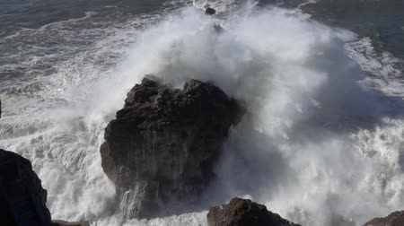 gigante : High waves breaking on rocks slow motion