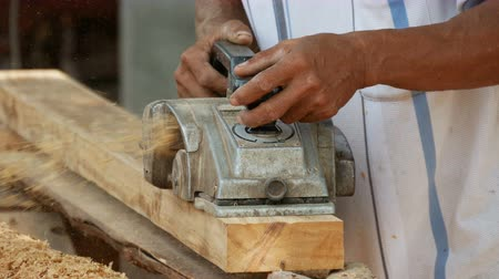 planing a plank of wood with a planer
