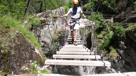 альпинист : Man walking wooden bridge on Via ferrata