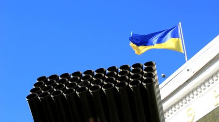 The trunk of the salvo fire system against the background of the sky and the flag of Ukraine.