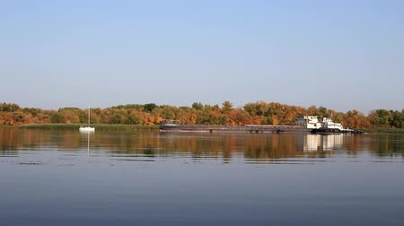 White yacht and barge are moving along the river in different directions, against the background of yellow trees.