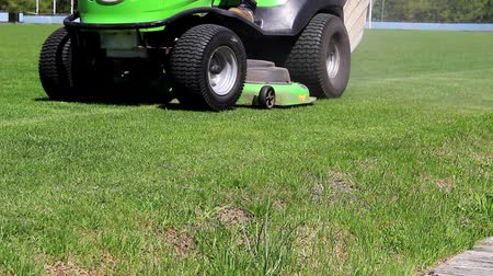 The lawnmower moves along the football field, stops, starts the work mode and moves on. Stock Footage