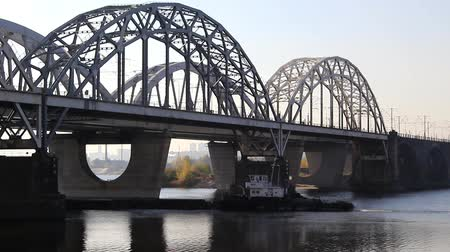 A bridge across the river with metal arches, beneath it a barge moves. Stock Footage