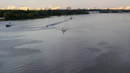 On the wide river, the ships move in different directions and the water scooter maneuvers between them at a fast speed.