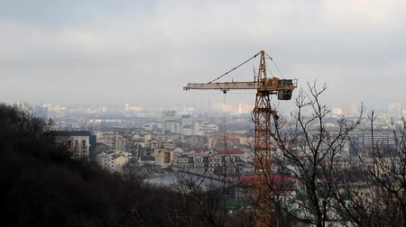 A construction crane installed on the mountain, in the background we see the left bank of the city and the slopes of the mountains.