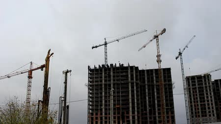 On the construction site, cranes are installed, they are deployed carrying the load in different directions.