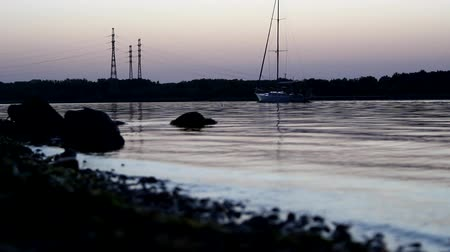 плотина : The yacht with the lowered sails. In the background, an island with towers of power lines installed on it.