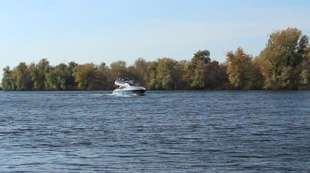 The boat moves slowly along the channel to the dam. Autumn yellow trees on the island Vidéos Libres De Droits
