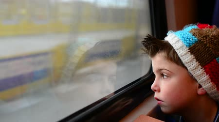 utazó :  boy in a moving train with his reflection in the window Stock mozgókép
