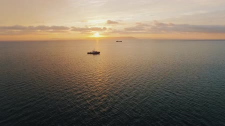 cinematic : Ship shoot by drones in the sea at sunset