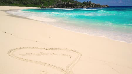 Small waves and huge boulders on the beach at Seychelles islands. La Digue, Anse Cocos. painted heart on the sand