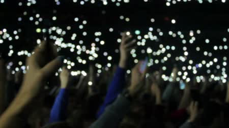 torcendo : People light fires on their phones at a concert. defocused footage