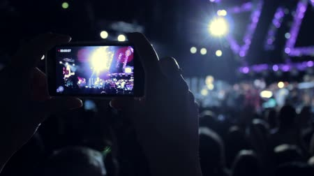 filmagens : Young woman filming concert on a phone Stock Footage