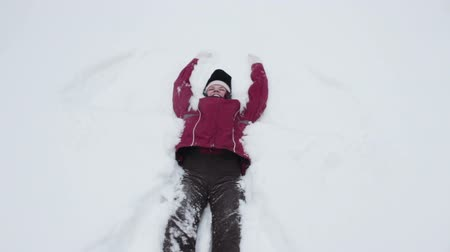 snow angel : Woman making snow angel Stock Footage