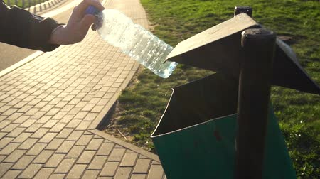 discard : womens hand throws an empty plastic bottle into the trash can