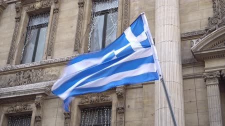 yunan : Greek flag waving on the strong wind on the background of buildings