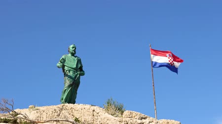 art : Makarska, Croatia. statue of St. Peter with a key symbol in his hands and the Croatian national flag Wideo