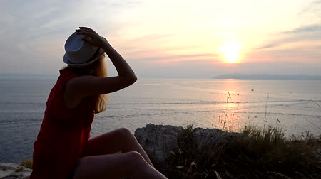 significado : Girl watching sunset over the sea thinking about the meaning of life Stock Footage