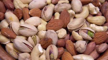 pinda s : close up. background of nuts. different types of nuts rotate in a circle