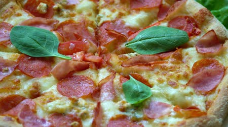 peperoni : close up. Pizza with tomatoes and cheese background rotating on the kitchen table