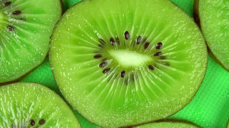 kivi : slice of juicy fresh kiwi rotates on the table in close-up