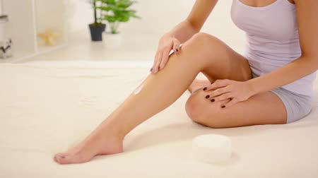 krém : Cropped video of a woman applying body lotion to her legs Dostupné videozáznamy