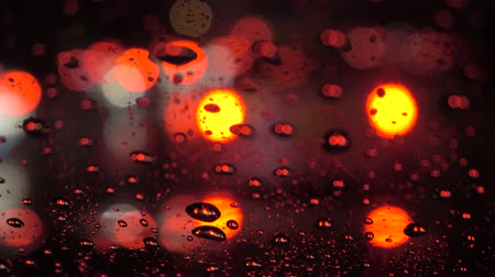 inside car : Traffic with rain at night : close up raindrop , car move and blink light